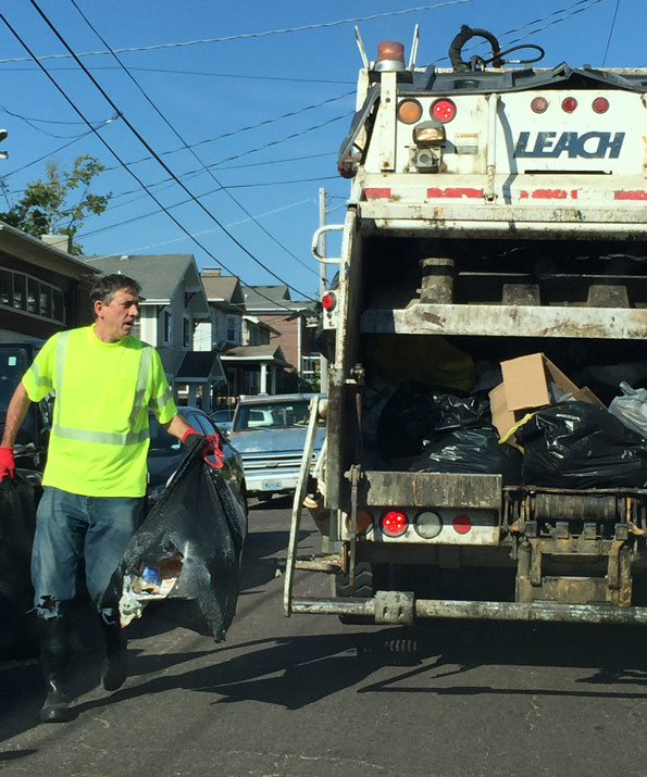 Ian Thomas working with city refuse collectors